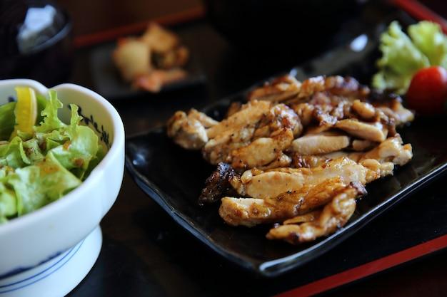 Grillowany ryż teriyaki z kurczaka na tle drewna