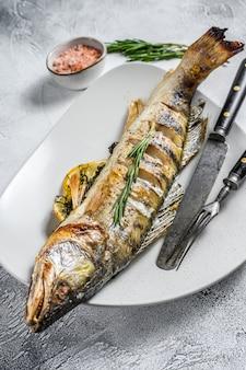 Grillowany sandacz, ryba walleye z ziołami i cytryna na talerzu