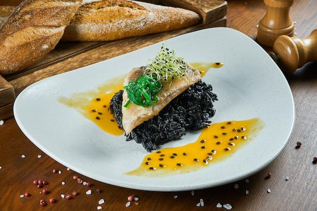 Grillowany sandacz z czosnkiem przyozdobionym czarnym ryżem i sosem mango na białym talerzu na drewnianym stole. zamyka w górę widoku na smakowitym owoce morza naczyniu