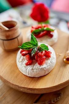 Grillowany ser camembert z listkami truskawek, miodu i bazylii, delikatesy, fondue z sera camembert na stole.