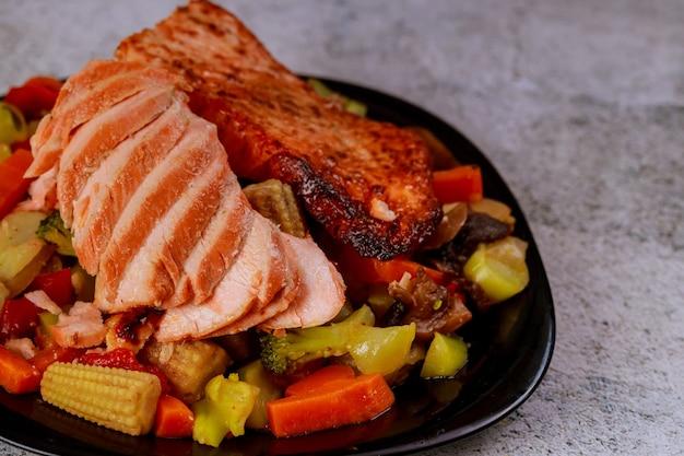 Grillowany soczysty filet z łososia z warzywami gotowanymi na parze na czarnym talerzu