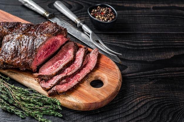 Grillowany stek butchers wybór wiszący onglet delikatne mięso wołowe na desce do krojenia. czarne drewniane tło. widok z góry. skopiuj miejsce.