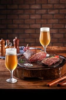 Grillowany stek cap rump na drewnianej desce do krojenia z dwoma szklankami piwa spocony zimny tulipa. drewniany stół i cegły w tle ściany (brazylijska picanha).