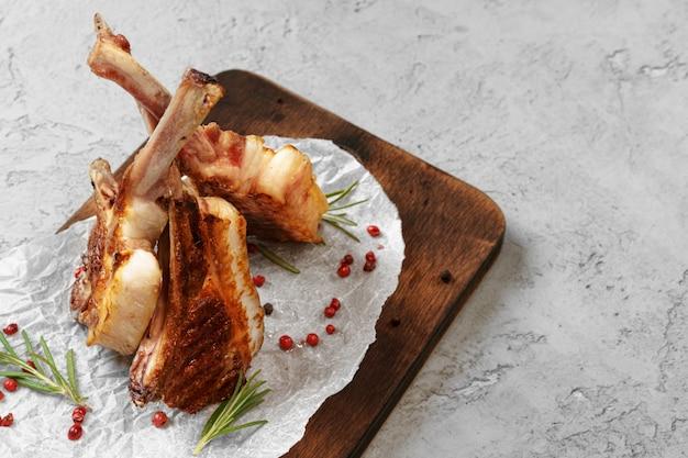 Grillowany stek jagnięcy podany na drewnianej desce. steki jagnięce
