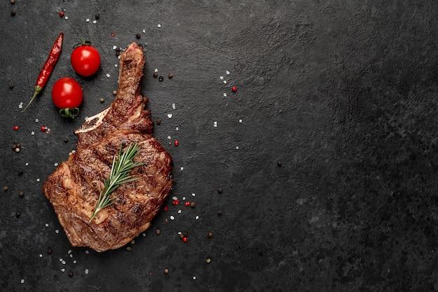 Grillowany stek kowbojski z przyprawami na kamiennym stole