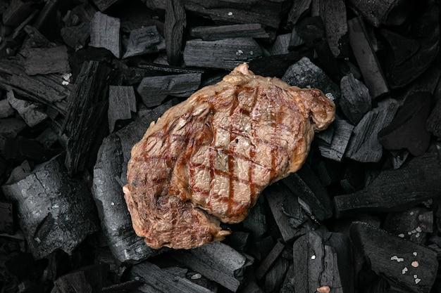 Grillowany stek na tle czarnego węgla drzewnego