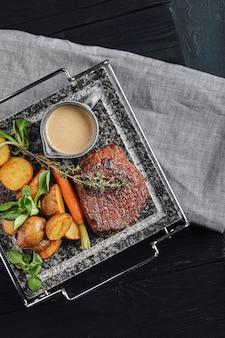 Grillowany stek ribeye na kamiennym grillu na ciemnym tle.