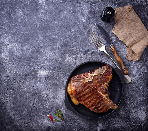 Grillowany stek t-bone na ciemnym tle
