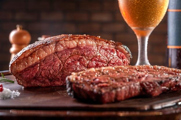 Grillowany stek w plasterkach cap rump z dwiema szklankami piwa na drewnianej desce do krojenia. marmurowa wołowina (brazylijska picanha).