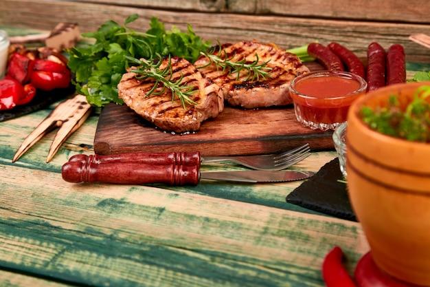 Grillowany stek wieprzowy na drewnianej desce do krojenia z różnorodnymi grillowanymi warzywami
