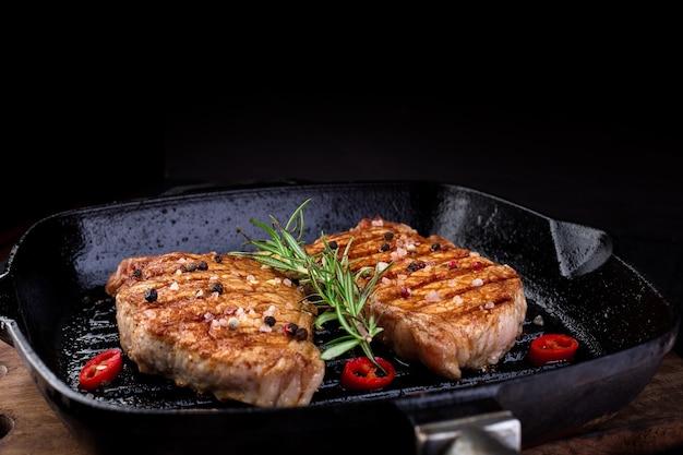 Grillowany stek wieprzowy na patelni grillowej z rozmarynem, papryczką chili i imbirem na drewnianej desce. skopiuj miejsce.