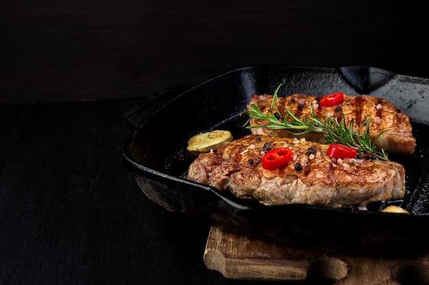 Grillowany stek wieprzowy na patelni grillowej z rozmarynem.