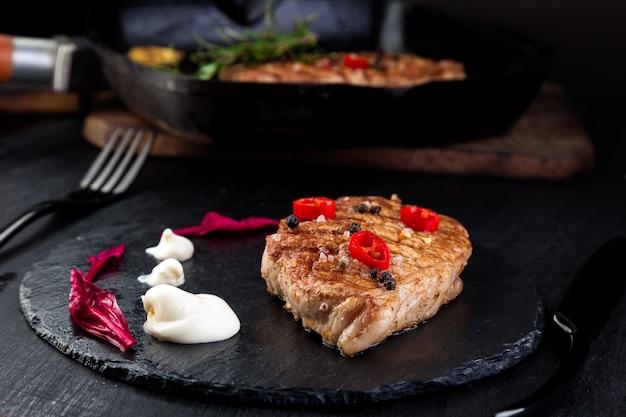 Grillowany stek wieprzowy na talerzu łupkowym.