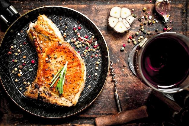 Grillowany stek wieprzowy z czerwonym winem. na drewnianym tle.