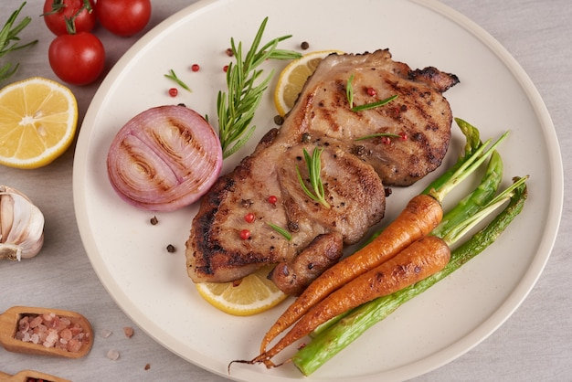 Grillowany stek wieprzowy z letniego grilla podawany z warzywami, szparagami, młodą marchewką, świeżymi pomidorami i przyprawami. grillowany stek na białym talerzu na kamiennej powierzchni. widok z góry.