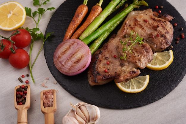 Grillowany stek wieprzowy z letniego grilla podawany z warzywami, szparagami, młodą marchewką, świeżymi pomidorami i przyprawami. grillowany stek na czarnym łupku na kamiennej powierzchni. widok z góry.