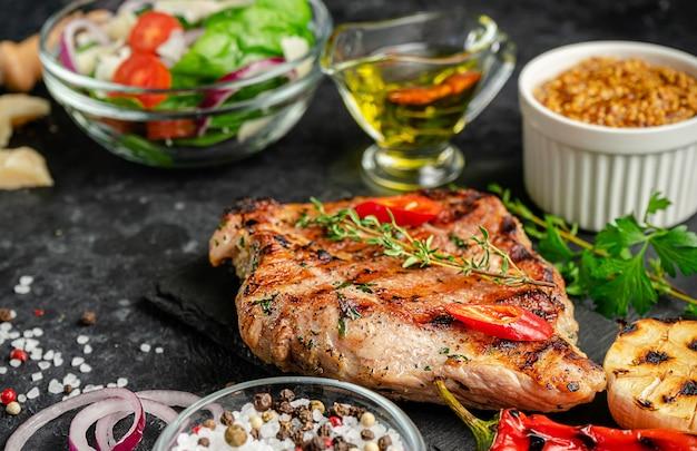 Grillowany stek wieprzowy z przyprawami i warzywami na ciemnym tle