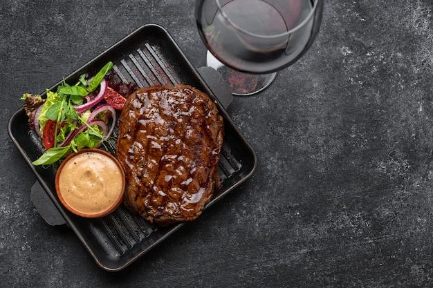 Grillowany stek wieprzowy z sosem kieliszek wina i warzywami na patelni z miejscem na tekst