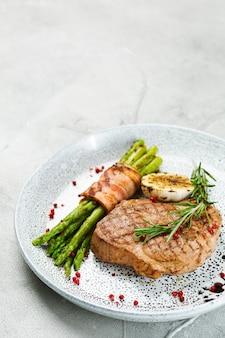 Grillowany stek wieprzowy ze szparagami i liściem rozmarynu na betonowym stole z bliska.