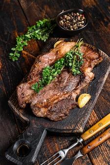Grillowany stek wołowy chuck eye roll na desce do krojenia. ciemne drewniane tło. widok z góry.