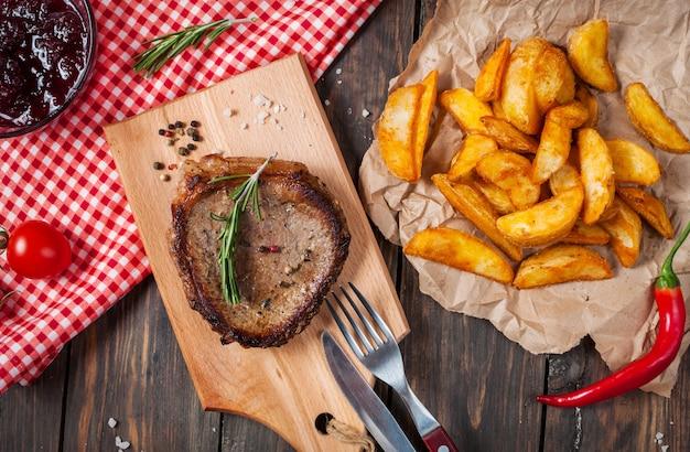 Grillowany stek wołowy doprawiony przyprawami podawany na drewnianej desce ze świeżym pomidorem cherry, pieczonymi ziemniakami i czerwoną ostrą papryczką chili.
