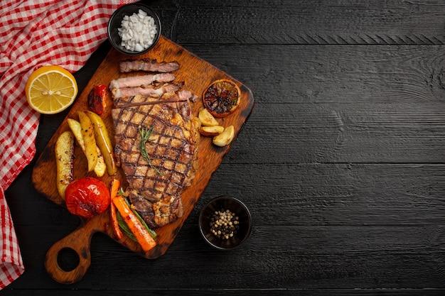 Grillowany stek wołowy na ciemnej drewnianej powierzchni.