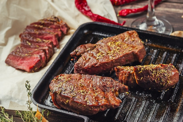 Grillowany stek wołowy na patelni, widok z góry. smażone kawałki mięsa z bliska