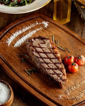 Grillowany stek wołowy podawany z ziołowymi solami i grillowanym pomidorem
