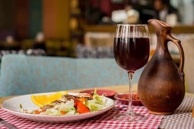 Grillowany stek wołowy ribeye z czerwonym winem, ziołami i przyprawami na drewnianym stole