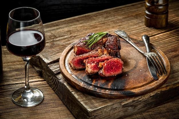 Grillowany stek wołowy ribeye z ziołami i przyprawami w czerwonym winie na drewnianym stole