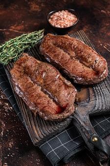 Grillowany stek wołowy shoulder top blade cut lub australia wagyu ostrygowy stek. ciemne tło. widok z góry.