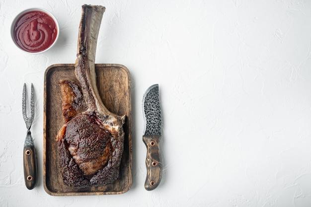 Grillowany stek wołowy tomahawk na drewnianej desce do serwowania widok z góry płaski leżał