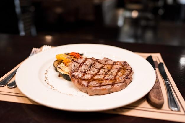 Grillowany stek wołowy z antrykotu z rozmarynowym pieprzem i solą grillowanymi warzywami na białym talerzu w restauracji