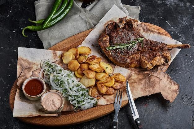 Grillowany stek wołowy z grilla tomahawk ze smażonym ziemniakiem