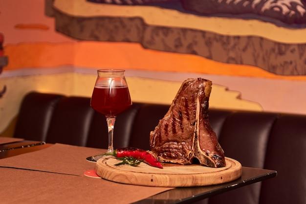 Grillowany stek wołowy z kością z gałązkami rozmarynu, pieprzem, solą i szklanką piwa w restauracji