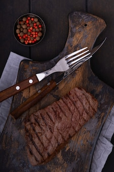 Grillowany stek wołowy z nożem i widelcem na desce do krojenia