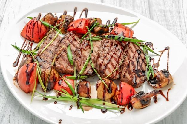 Grillowany stek wołowy z pieczarkami i pomidorami. koncepcja zdrowego odżywiania.