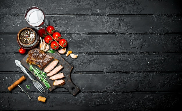 Grillowany stek wołowy z rozmarynem i pomidorami. na czarnej rustykalnej powierzchni.
