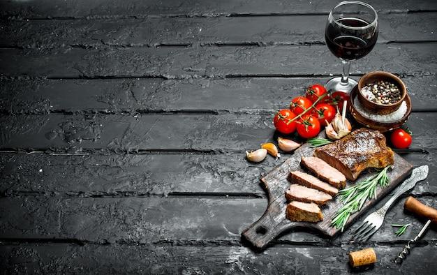 Grillowany stek wołowy z rozmarynem i pomidorami. na czarnym rustykalnym stole.