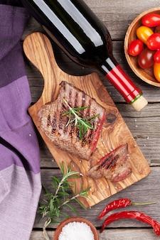 Grillowany stek wołowy z rozmarynem, solą, pieprzem i butelką wina na drewnianym stole. widok z góry
