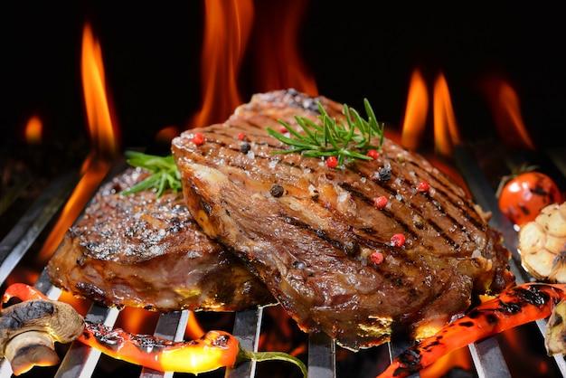 Grillowany stek wołowy z warzywami na płonącym grillu
