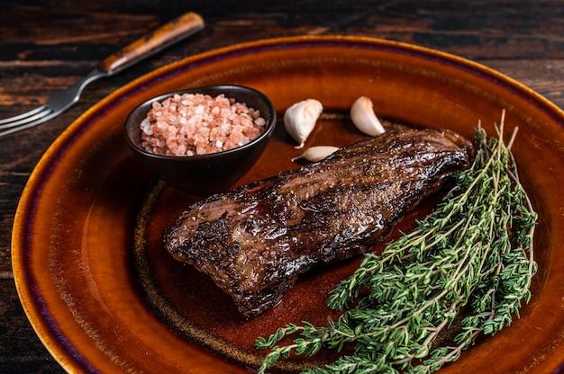 Grillowany stek wołowy ze spódnicą maczety na rustykalnym talerzu z ziołami i różową solą. ciemne tło drewniane. widok z góry.