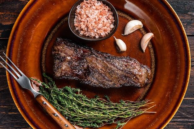 Grillowany stek wołowy ze spódniczką maczety na rustykalnym talerzu z ziołami i różową solą