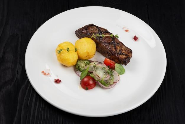 Grillowany stek wołowy ze spódniczką z ziemniakami i warzywami na białym talerzu na drewnianym czarnym tle