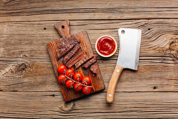 Grillowany stek wołowy ze świeżym sosem pomidorowym na desce do krojenia