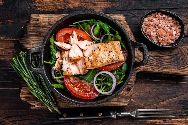 Grillowany stek z fileta z łososia ze świeżą rukolą sałatkową, awokado i pomidorem na patelni. ciemne tło drewniane. widok z góry.