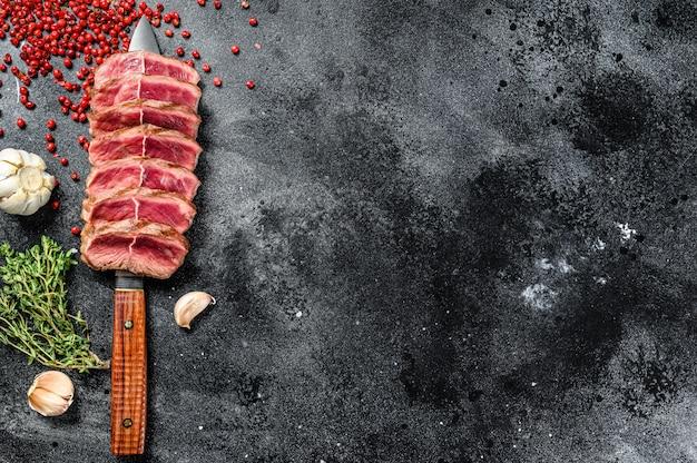 Grillowany stek z grilla z górnym ostrzem. organiczne mięso wołowe na czarno. widok z góry. skopiuj miejsce