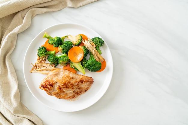 Grillowany stek z kurczaka z warzywami na białym talerzu