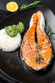 Grillowany stek z łososia przyozdobiony ryżem i szpinakiem. widok z góry