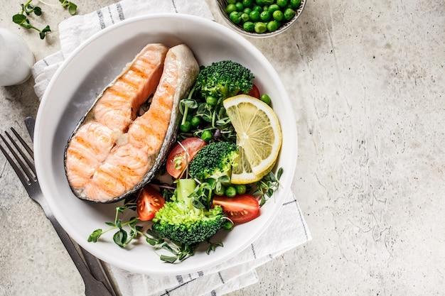 Grillowany stek z łososia z brokułami i pomidorami w białym talerzu na szaro
